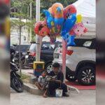 Indonesia: un niño le enseña a leer a su hermanito mientras vende globos para sobrevivir.