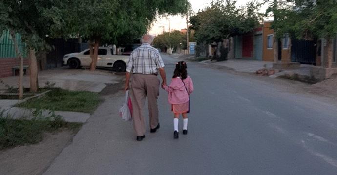 Bisabuelo lleva a su nieta el primer día de clases. Un ángel guardián.